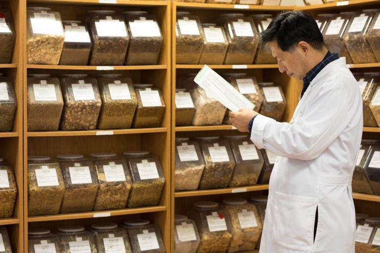An image of Dr. Lao looking through reports in front of the herb shelf