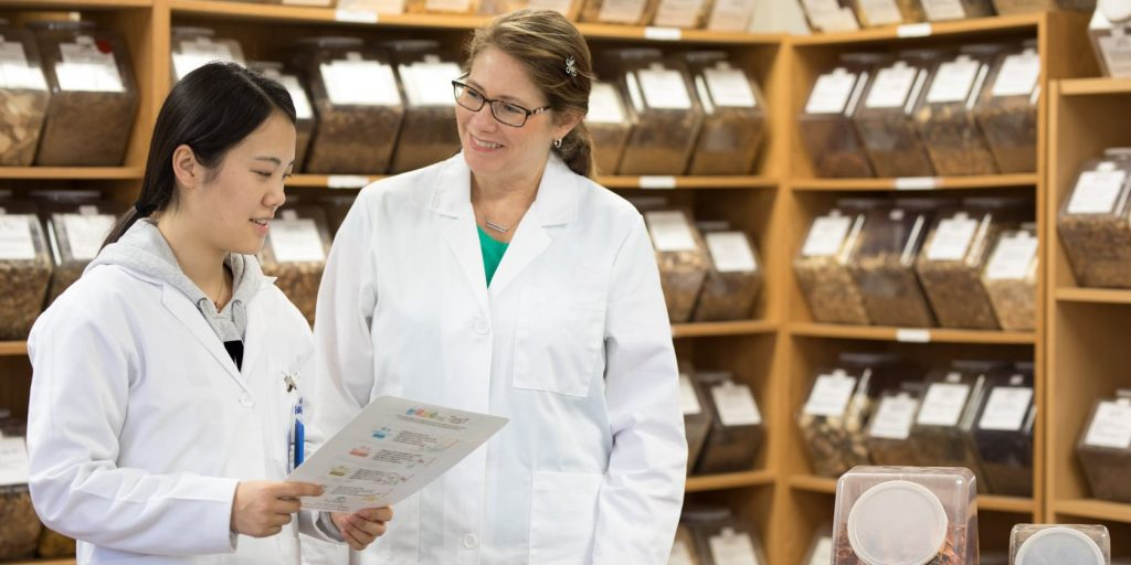 An image of a student talking to a professor in front of the herb shelf